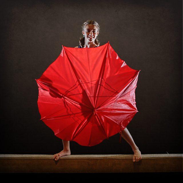 Gymnast posing with red umbrella