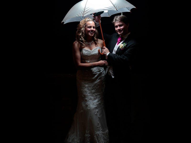 Bride and groom under white flashlit umbrella