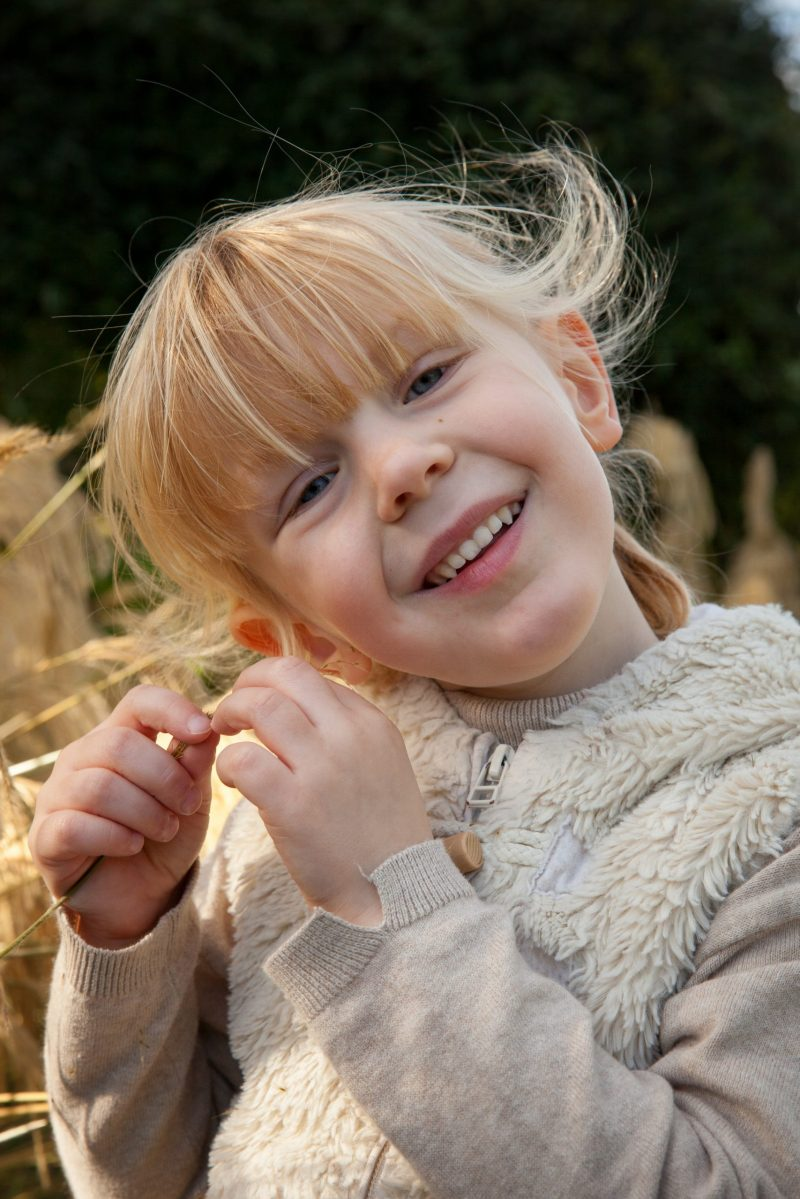 Young fair skinned girl playing with grass