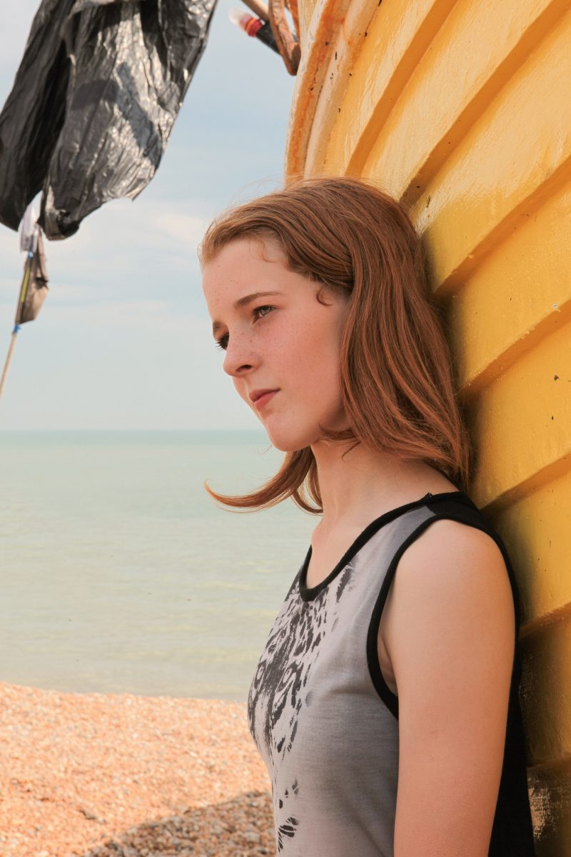Portrait of adolescent girl leaning against yellow hull of boat
