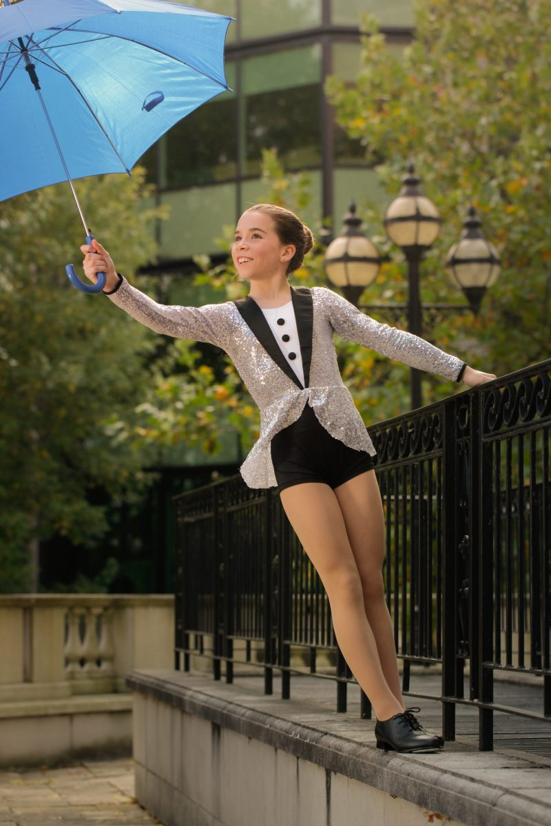 Older girl in tap dance waistcoat and blue umbrella