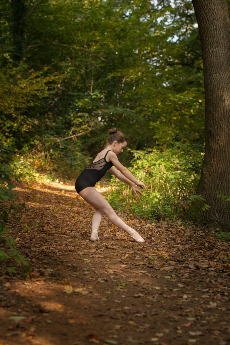 Older girl ballet dancing in woods