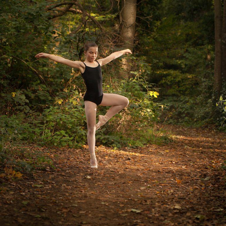 Older girl ballet dancing in woods