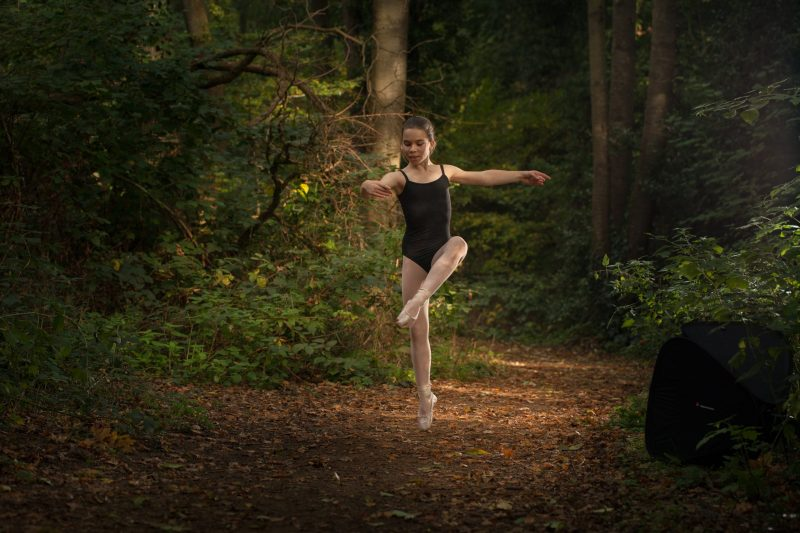 Older girl ballet dancing in woodland