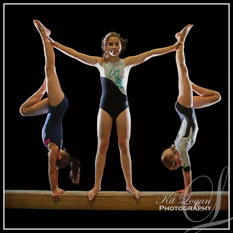 3 young female gymnasts posing on beam