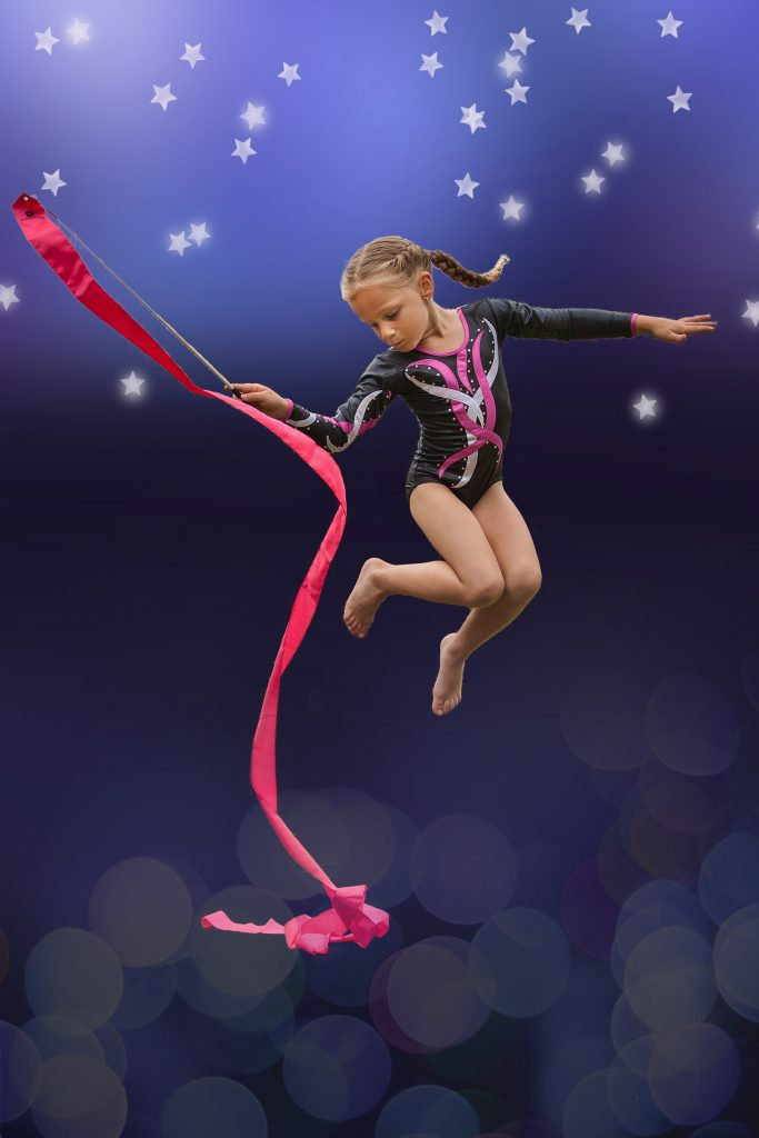 Young gymnast in pose with dance ribbon midair