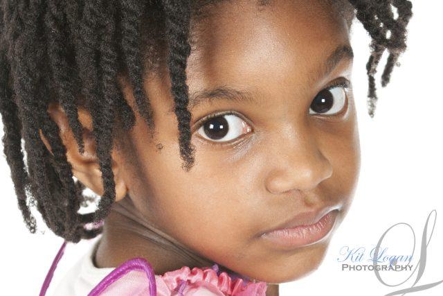 Studio portrait of young dark skinned girl