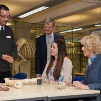 HRH Duchess of Cornwall sitting with student looking at bones