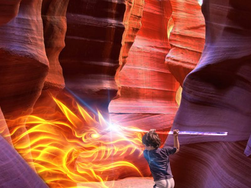 photo manipulation of young boy in scenic canyon fighting a dragon of fire