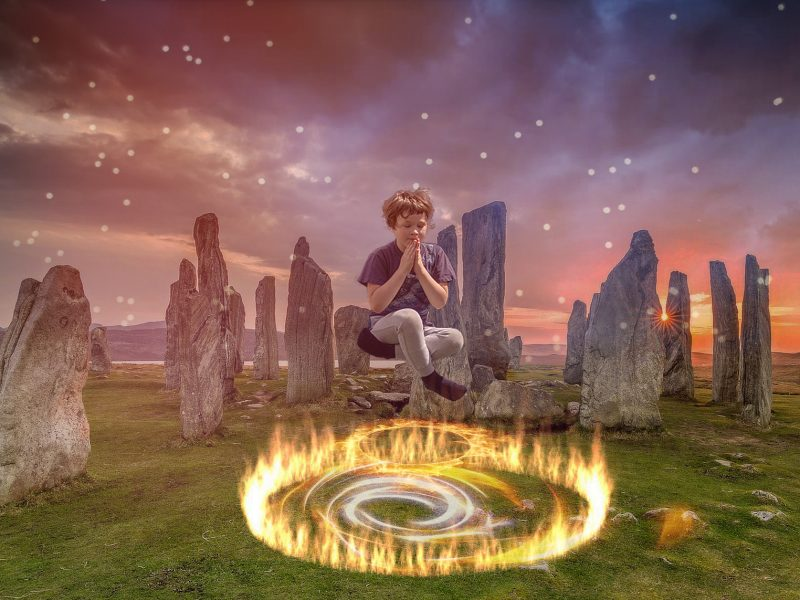 Photo manipulation. Young boy sitting crosslegged in air meditating over rings of fire