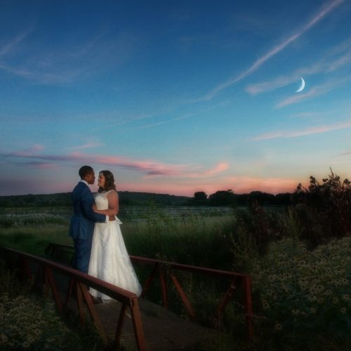 bride and groom against evening sky