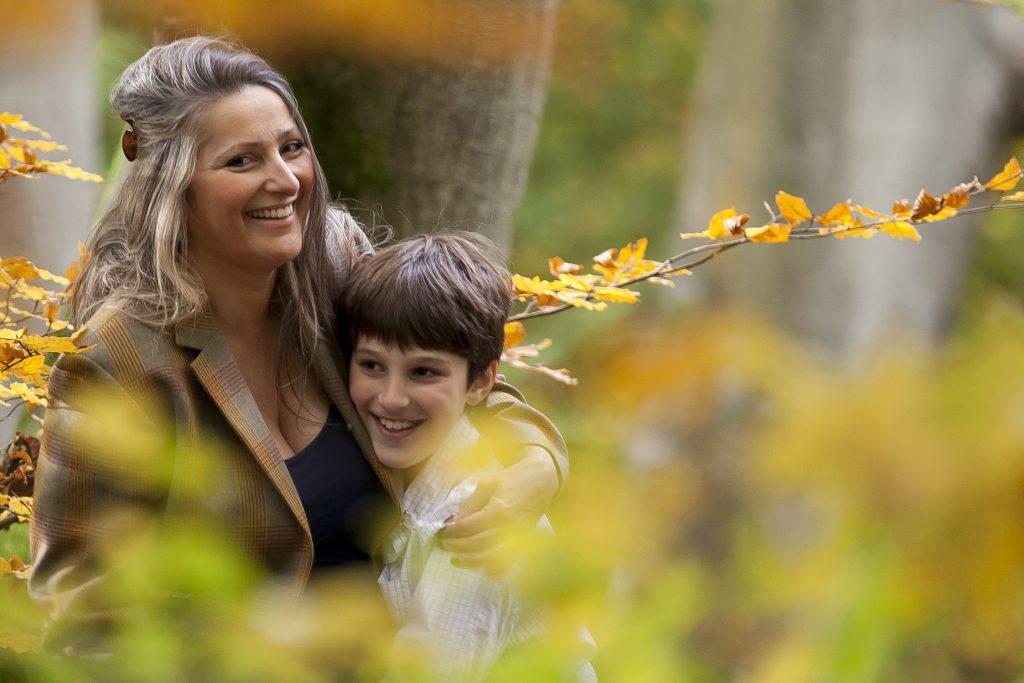 mother with son in autumnal woodland