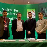 Sir Robert Winston standing with others at the Society for Reproduction Fertility stall