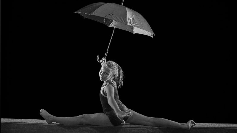 young gymnast posing on beam with umbrella