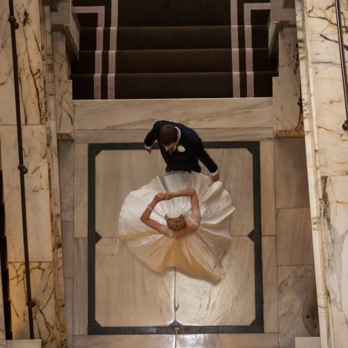 arial view of bride and groom in marble stair well