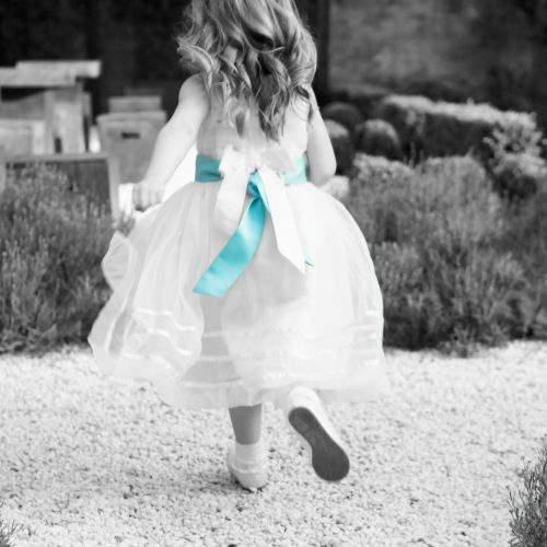 black and white image of young bridesmaid running blue sash detail