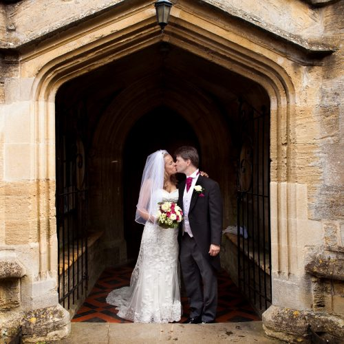 bride and groom kissing in church arch