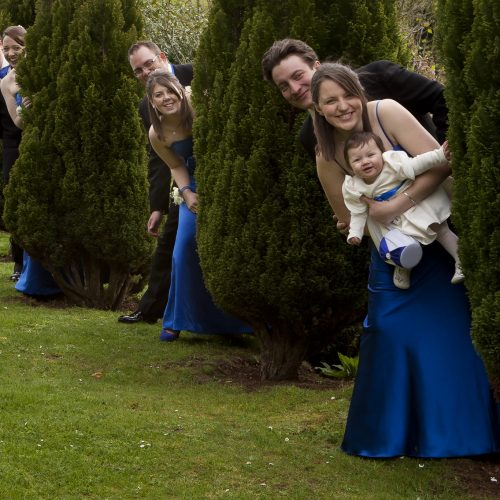 bridesmaids and best men posed by hedges
