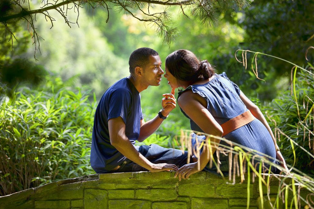 coloured young couple sitting on small bridge about to kiss