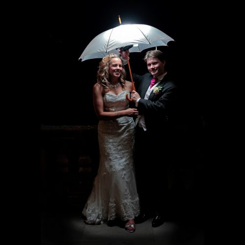 bride and groom under a lighted umbrella